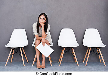 Tired of waiting. Bored young businesswoman holding paper and looking away while sitting on chair against grey background