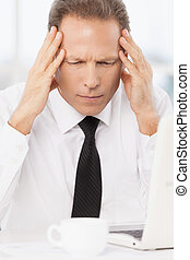 Tired of work. Depressed mature man in shirt and tie drinking holding head in hands while sitting at his working place