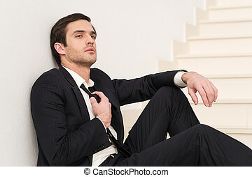 Tired of work. Side view of thoughtful young man in formalwear adjusting his necktie while sitting on staircase