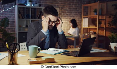 Tired office worker using computer feeling headache sleeping on desk at night