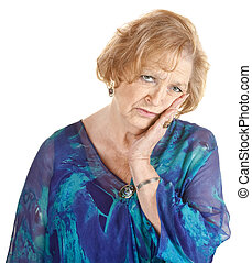 Tired older woman in blue with hand on cheek