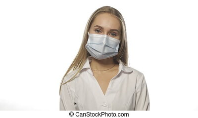 Tired or careless nurse in protective mask and medical hospital robe looking at camera isolated on white. High quality 4k resolution footage.