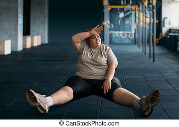 Tired overweight woman sits on the floor in gym