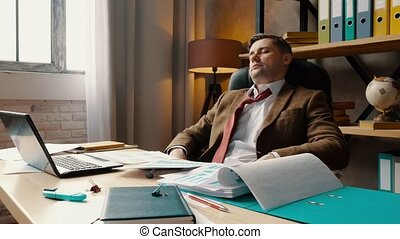 Tired, overworked businessman relaxes while sitting on chair. Exhausted man in the office.