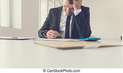 Tired overworked businessman sitting at his desk supporting his head with the arm
