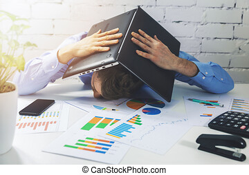 tired overworked office worker sleeping on the desk with laptop over head