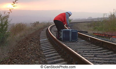 Tired passenger with suitcases sitting on railroad track at...