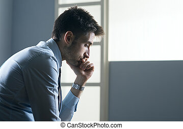 Tired pensive businessman with hand on chin.