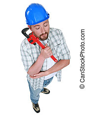 Tired plumber holding wrench