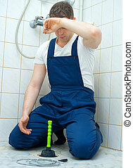 Tired plumber repairing bathroom with hand plunger.