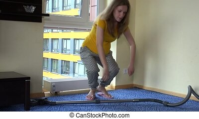 Tired pregnant woman hoover vacuum clean room and sit on...