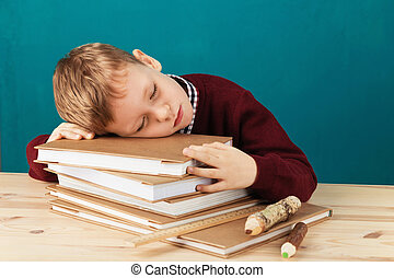 tired school boy asleep on books. little student sleeping on textbooks. Child in school uniform lies on the table with big pile of books against blue wall. Eyes closed. School concept.