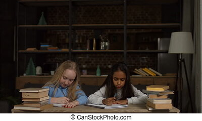 Tired school girls studying with a pile of books