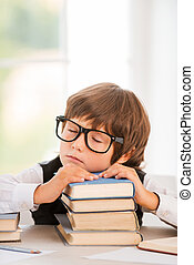 Tired schoolboy. Cute young boy sleeping while sitting at the table and leaning his face at book stack