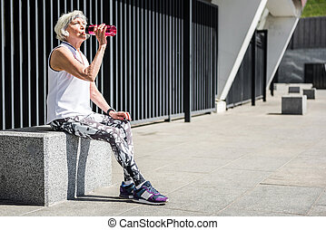 Tired senior lady having rest after exercise beside metal fence