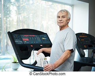 Tired senior man on a treadmill with towel and bottle of...