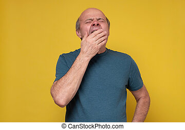 Tired senior man yawning feeling fatigued, lack of energy