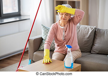 tired senior woman cleaning table at home