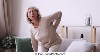 Tired senior woman feels sudden back pain at home. Unhealthy old lady touching spine muscles having lower lumbar ache sitting on sofa. Upset elder grandma suffering from backache. Osteoarthritis concept