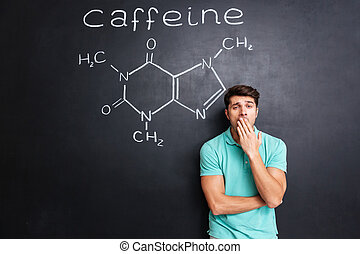 Tired sleepy man yawning over blackboard with drawn caffeine molecule