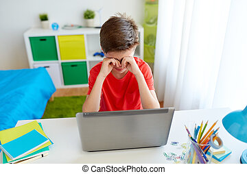 tired student boy with laptop computer at home
