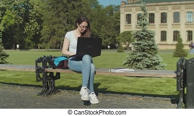 Tired student falling asleep with laptop on bench -...