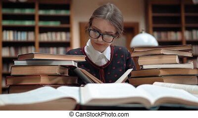 Intellectual student got tired while doing homework, good-looking girl, in lovely dark blue sweater with red hearts, scanning the book text, indoor shot among tons of books in library