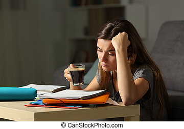 Tired student studying late hours drinking coffee