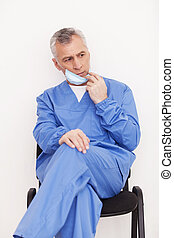 Tired surgeon. Depressed senior grey hair doctor taking off his surgical mask while sitting at the chair