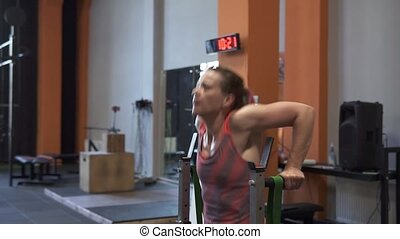 Tired sweaty fitness woman doing bar dips workout in gym