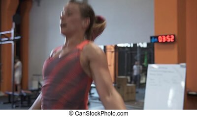 Tired sweaty fitness woman doing double jumping rope workout in gym