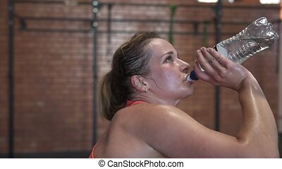 Tired sweaty fitness woman drinks water from a bottle during workout in gym