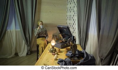 Tired tailor girl have a rest, drinks tea, relaxes, listens music on vinyl plate, gramophone or phonograph. Retro seamstress woman works at home or workshop at evening or night with kerosene lamp