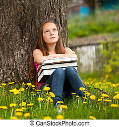 Tired teen girl with books in the village