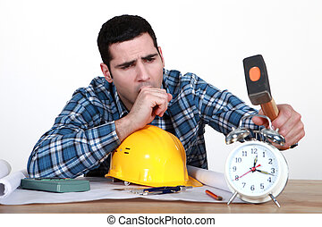 Tired tradesman about to smash his alarm clock