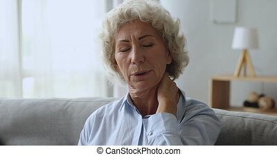 Tired upset middle aged woman suffering from neck pain.