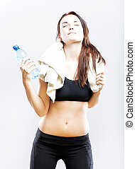Tired woman after fitness with towel and water bottle