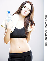 Tired woman after fitness with water bottle and towel