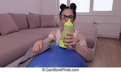 Tired woman after workout near stability ball