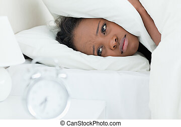 Tired woman covering her ears while her alarm clock is ringing