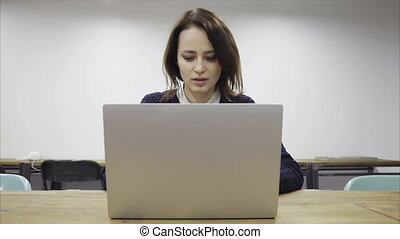 Tired woman is working late in the empty office, closing a laptop and putting the head on the table