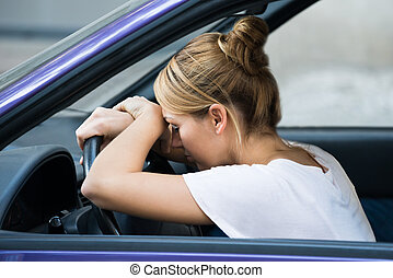 Tired Woman Leaning On Steering Wheel In Car