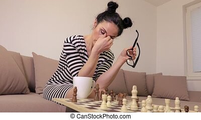 Tired woman playing chess
