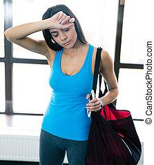Tired woman standing with bag