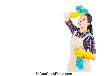 Tired woman standing with cleaning supplies - Tired young...