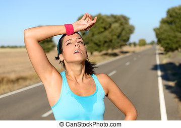 Tired woman sweating after running