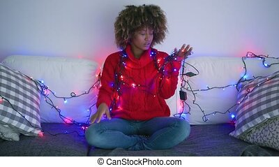 Tired woman trying to untangle garland - Young ethnic model...