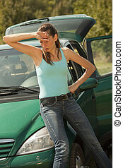 Tired woman with a broken car