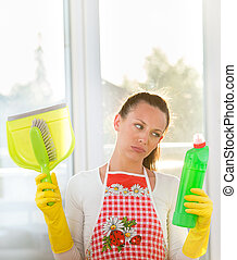 Tired woman with cleaning equipment - Tired young woman with...