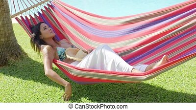Tired woman with grin laying in hammock - Tired beautiful...